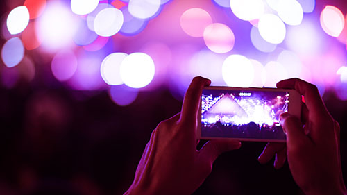 blurry colorful background of hand holding smart phone to taking photo people crowded in concert.